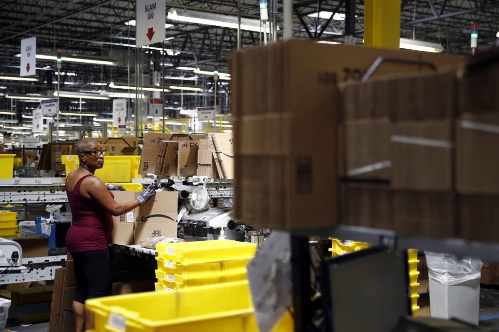 In this Aug. 3, 2017, file photo, Cynthia Richburg prepares a product for shipment at an Amazon fulfillment center in Baltimore. Amazon is boosting its minimum wage for all U.S. workers to $15 per hour starting next month. The company said Tuesday, Oct. 2, 2018, that the wage hike will benefit more than 350,000 workers, which includes full-time, part-time, temporary and seasonal positions. (AP Photo/Patrick Semansky, File)