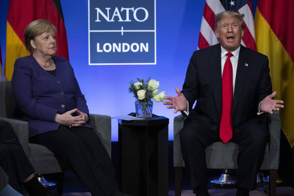 President Donald Trump meets with German Chancellor Angela Merkel during the NATO summit at The Grove, Wednesday, Dec. 4, 2019, in Watford, England. (AP Photo/ Evan Vucci)