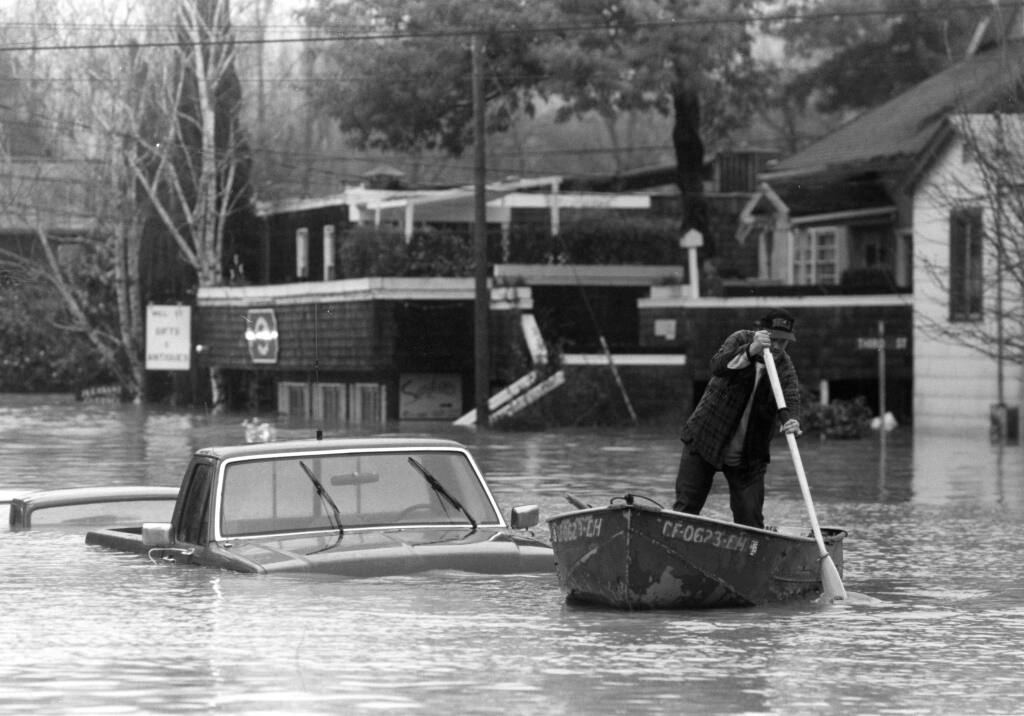 The Russian River crested over 48 feet at Guerneville bridge in 1995. In this photo a local paddles among water logged autos on Main Street. (Chad Surnick/ The Press Democrat)