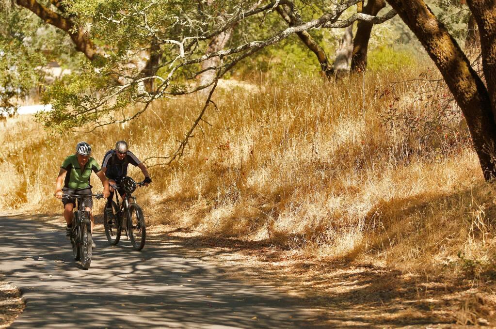 Sonoma locals Michael Cullen, left, and Scot Hunter pedal uphill on Orchard Road in the wilderness area behind Sonoma Developmental Center, in Eldridge, California on Saturday, July 23, 2016. (Alvin Jornada / The Press Democrat)