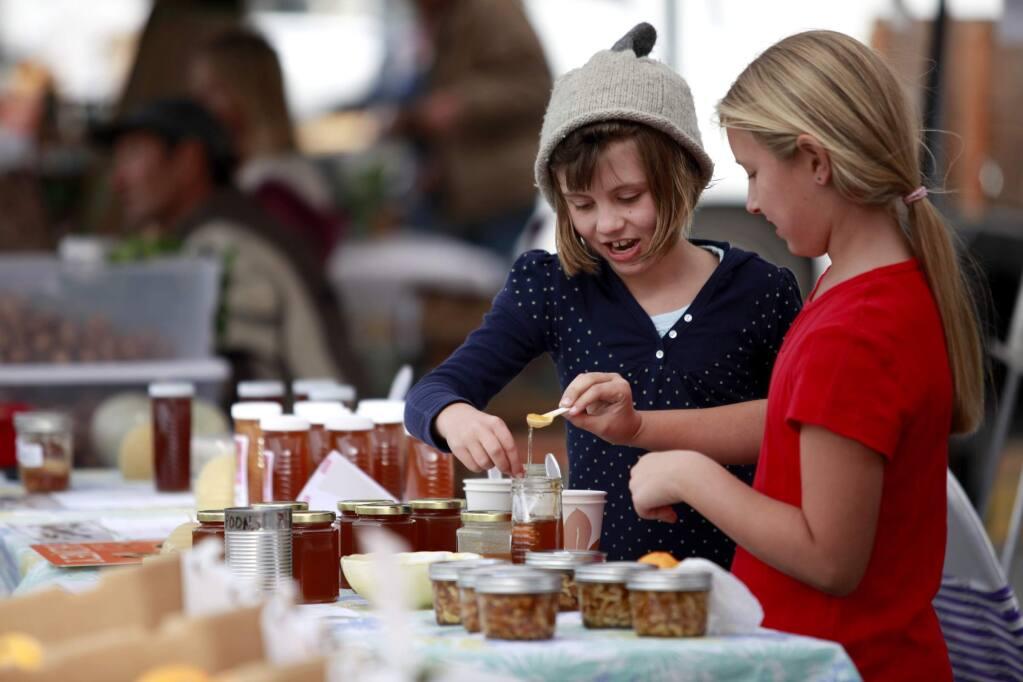 Gwyneth Barker, 7, left, and Amber Vanoni, 8, taste honey from the Beelove Honey during the West End Farmers Market in Santa Rosa, California on Sunday, November 3, 2013. (BETH SCHLANKER/ The Press Democrat)