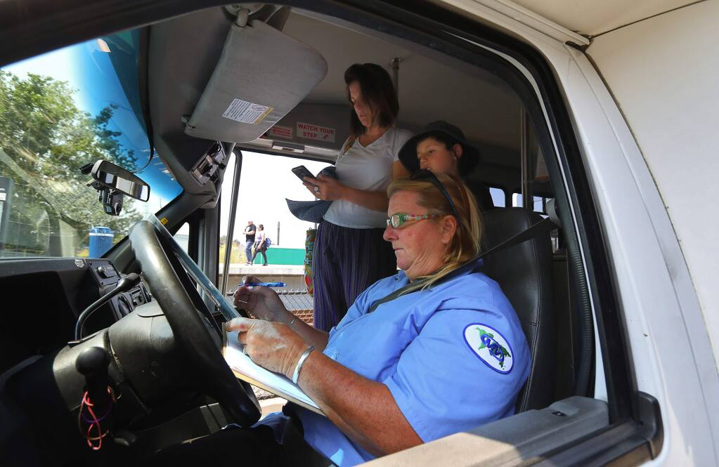 Santa Rosa ParkSMART shuttle bus driver Sherry Friscia tells passengers Cristina and Samuel Lozano where they can be dropped off on her route through downtown Santa Rosa on Tuesday, August 14, 2018. (Christopher Chung/ The Press Democrat)
