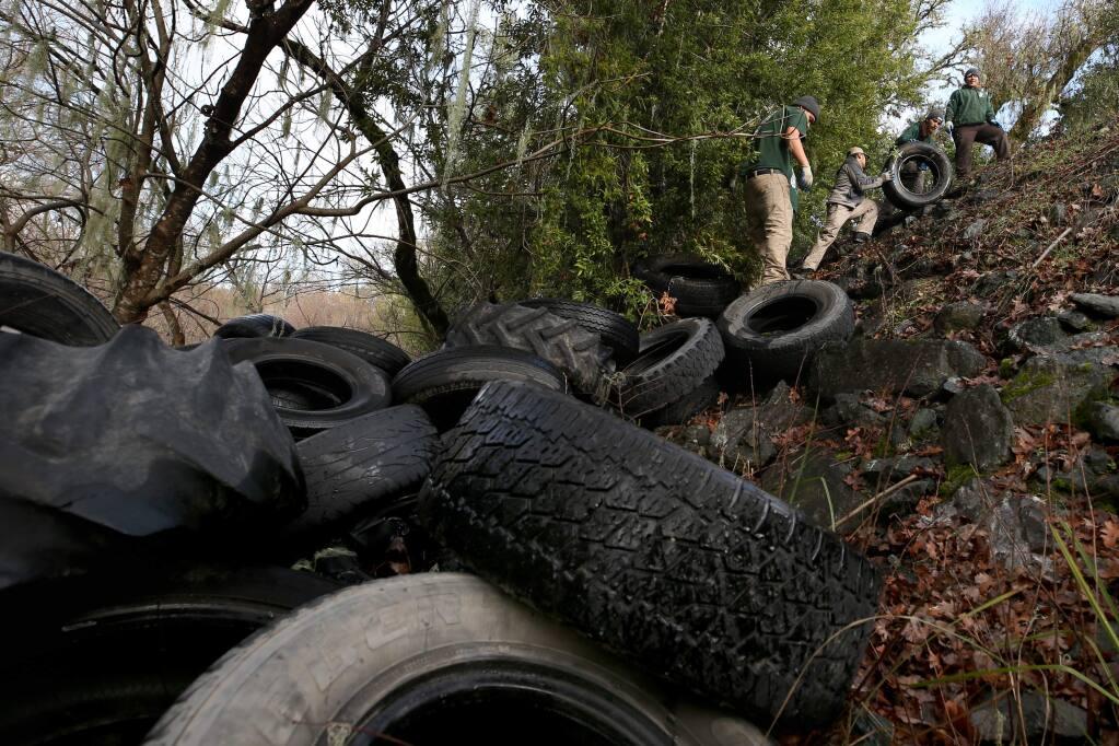 Conservation Corps personnel work to clean up about 250 tires dumped near the Russian River off Hwy 101 just south of Hopland on Thursday, January 9, 2020. (BETH SCHLANKER/ The Press Democrat)