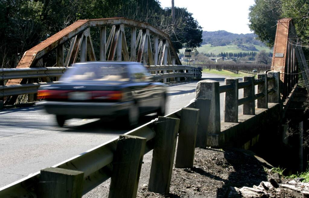 A car drives over the Watmaugh Road Bridge in Sonoma, one mile south of the Plaza. Safety concerns have forced the county to plan the bridge's replacement, despite the fondness many Sonomans have for such historic structures. (BETH SCHLANKER/ The Press Democrat)