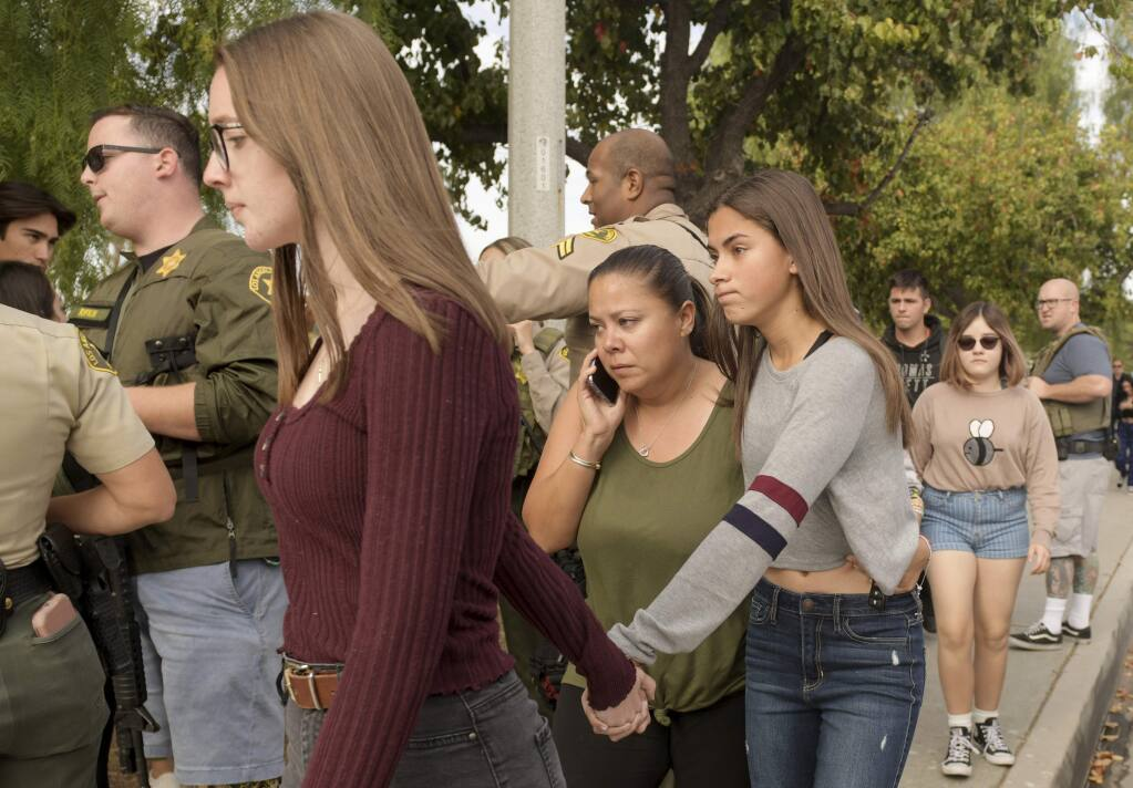 Students evacuate their campus after reports of a shooting at Saugus High School on Thursday, Nov. 14, 2019 in Santa Clarita, Calif. The shooting occurred around 7:30 a.m. at the high school, about 30 miles (48 kilometers) northwest of downtown Los Angeles. (AP Photo by Christian Monterrosa)