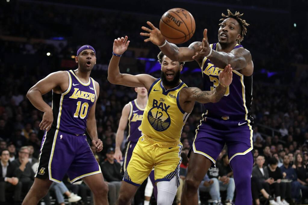 The Los Angeles Lakers' Dwight Howard, right, grabs a rebound over the Golden State Warriors' Ky Bowman during the first half Wednesday, Nov. 13, 2019, in Los Angeles. (AP Photo/Marcio Jose Sanchez)