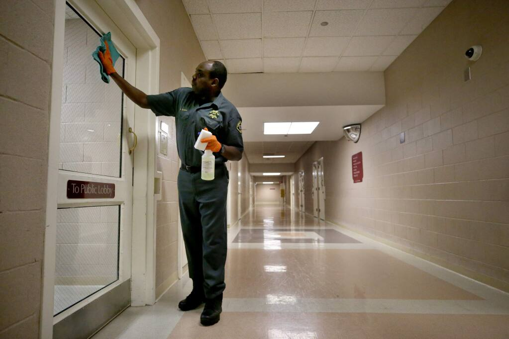 Janitor David Kilonzo sanitizes surfaces to try and prevent the spread of COVID-19 at the Sonoma County Main Adult Detention Facility in Santa Rosa on Sunday, March 15, 2020. (Beth Schlanker / The Press Democrat)