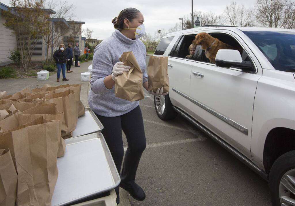 Irma Alvarado Pizano hands breakfast and lunch bags to a student's parents at the drive-through at Adele Harrison Middle School on Monday, Mar. 23. (Photo by Robbi Pengelly/Index-Tribune)