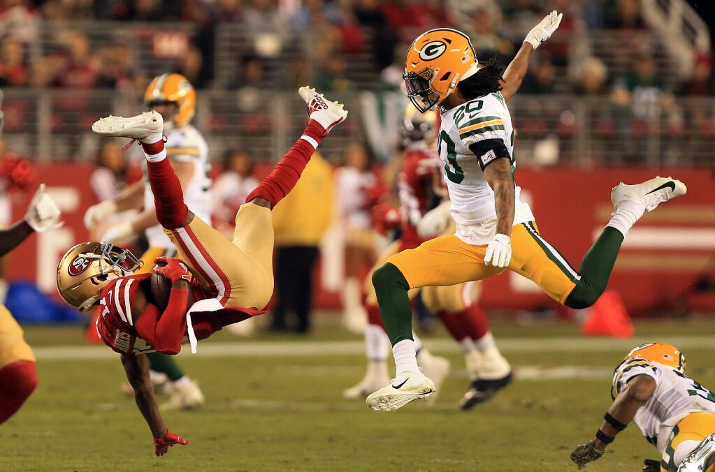Emmanuel Sanders of the 49ers vaults to a first down as Kevin King of the Packers pursues, during San Francisco's 37-8 win over Green Bay, Sunday, Nov. 24, 2019 in Santa Clara. (Kent Porter / The Press Democrat) 2019