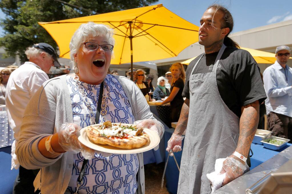 Robin Finkelstein, left, of Santa Rosa beams after being complimented on making one of the best looking pizzas of the day, as Worth Our Weight grillmaster Lukas Falcon, right, looks on, during the North Coast Food and Wine Festival at SOMO Village in Rohnert Park, California, on Saturday, June 10, 2017. (Alvin Jornada / The Press Democrat)