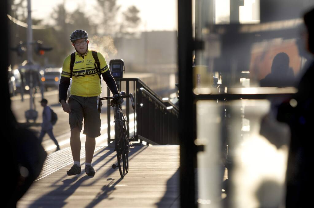 Jonathan Cole, headed to work in San Anselmo, walks with his bike at the SMART station in Petaluma, on Wednesday, November 29, 2017. (BETH SCHLANKER/ The Press Democrat)