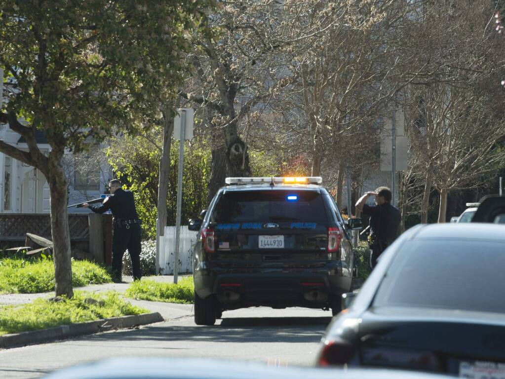 Santa Rosa Police officers with guns drawn move toward the car of a shooting suspect who had ditched his car on the corner of Beaver Street and College Avenue on Thursday, Feb. 23, 2017. (ERIK CASTRO/ FOR THE PD)