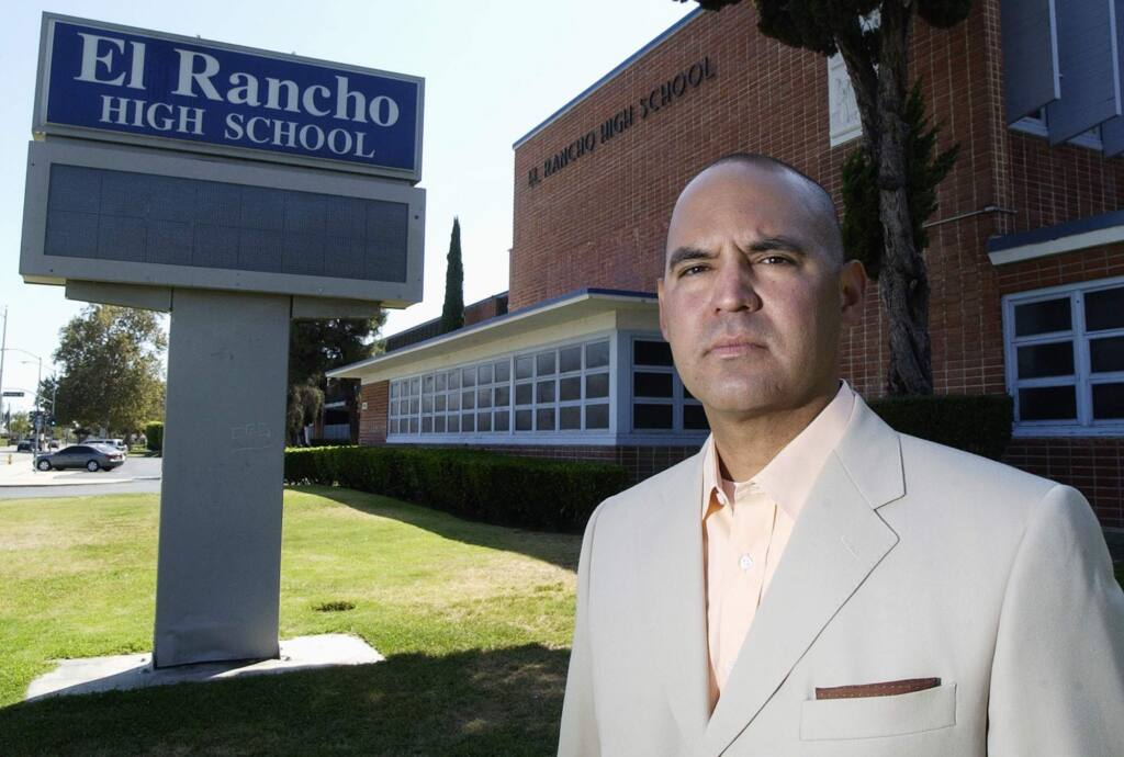 In this July 21, 2010, photo, teacher Gregory Salcido stands in front of El Rancho High School in Pico Rivera, Calif., after a complaint has been filed against him. White House Chief of Staff John Kelly says the Los Angeles-area high school teacher 'ought to go to hell' for disparaging U.S. military service members in classroom remarks. (Keith Durflinger/Los Angeles Daily News via AP)