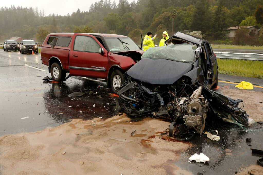 California Highway Patrol officers Mike Ball, left, and Crandon Kopriva investigate the scene of a fatal accident on northbound Highway 101, past the Geyserville Avenue exit in Geyserville, California, on Friday, March 22, 2019. (Alvin Jornada / The Press Democrat)