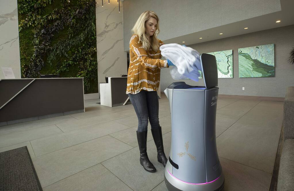 Brooke Ross, director of sales and marketing for Hotel Trio, loads towels and a bag of ice into Rose the Butler, a robot programmed to deliver items to guest rooms. The robot has helped with the social distancing at the Healdsburg hotel. (photo by John Burgess/The Press Democrat)