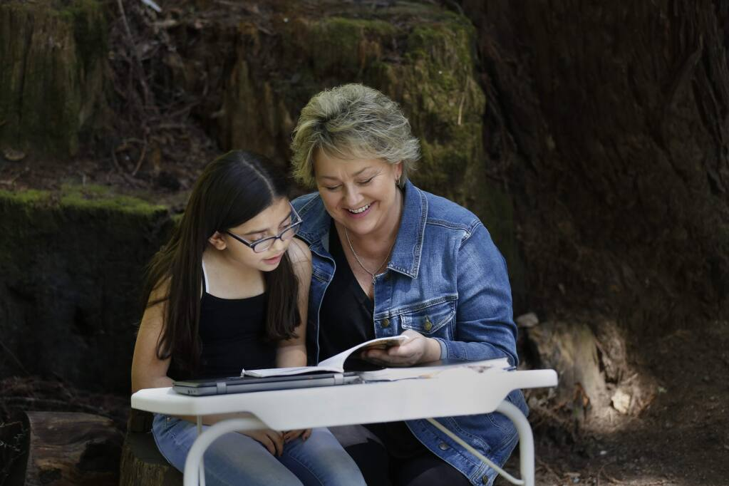 Cynthia Ferrera, a parent liaison at Lilliput Children's Services and her granddaughter, Tatianna Rodriguez, 8, read together in an outdoor classroom set up outside their home in Rio Nido on Thursday, April 23, 2020. (BETH SCHLANKER/ The Press Democrat)