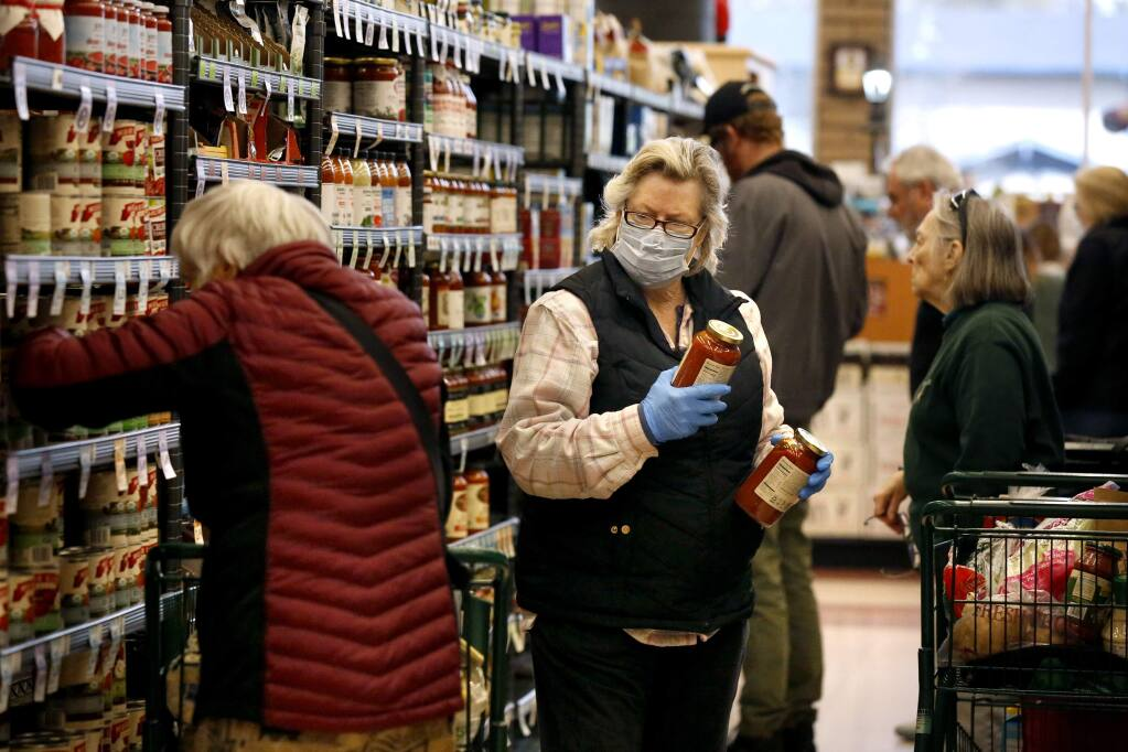 Belinda, who wished not to give her last name, takes precautions with a mask and gloves as she shops in the canned good aisle at Oliver's Market in the Montecito Center in Santa Rosa on Tuesday, March 17, 2020. (Beth Schlanker / The Press Democrat)