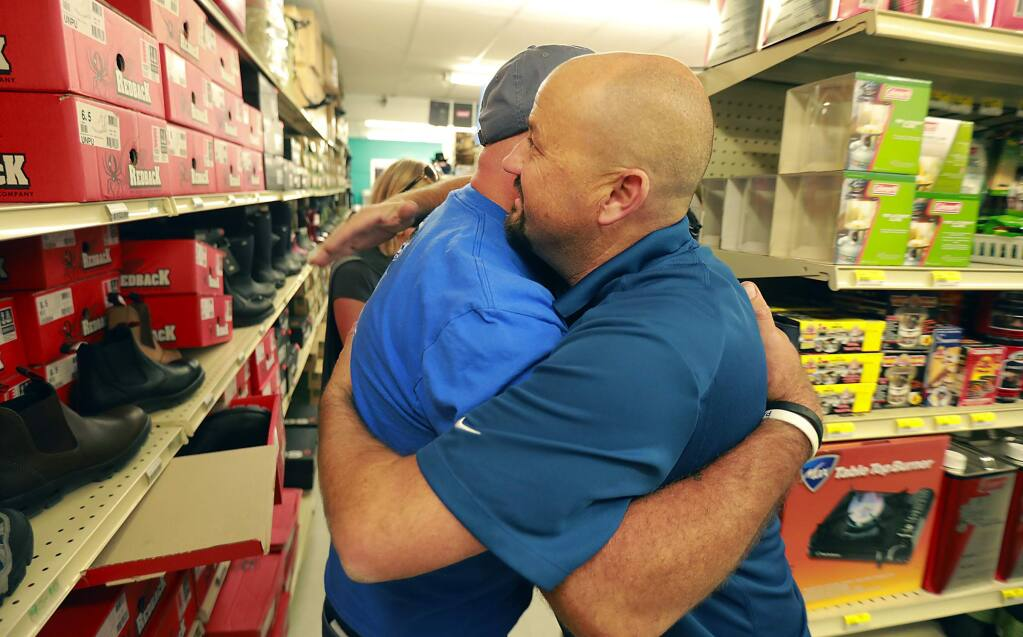 Brad Silvestro hugs Sebastopol ACE hardware general manager Dan Allingham after he was told the store would donate his work boots and all the clothing he wanted after eh and his wife lost their home off Deer Trail Rd. in Rincon Valley. (photo by John Burgess/The Press Democrat)
