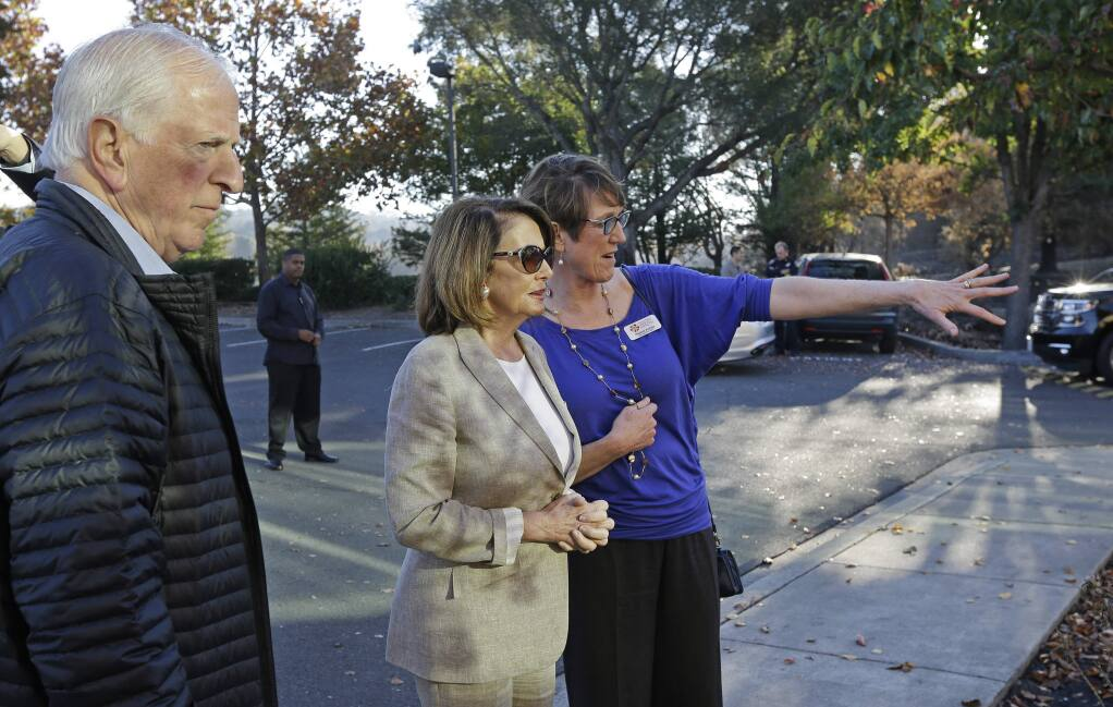 Naomi Fuchs, right, CEO of Santa Rosa Community Health, gestures beside Minority Leader Nancy Pelosi, D-Calif., and Rep. Mike Thompson, D-Calif., during a tour of the wildfire affected Vista campus on Saturday, Oct. 28, 2017, in Santa Rosa, Calif. (AP Photo/Ben Margot)
