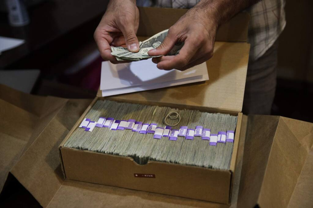 FILE - In this June 27, 2017 file photo, the proprietor of a medical marijuana dispensary prepares his monthly tax payment, over $40,000 in cash, at his Los Angeles store. A proposal in Congress to ease the federal ban on marijuana could encourage more banks to do business with cannabis companies, but it appears to fall short of a cure-all for an industry that must operate mainly as a cash business in a credit card world. (AP Photo/Jae C. Hong, File)