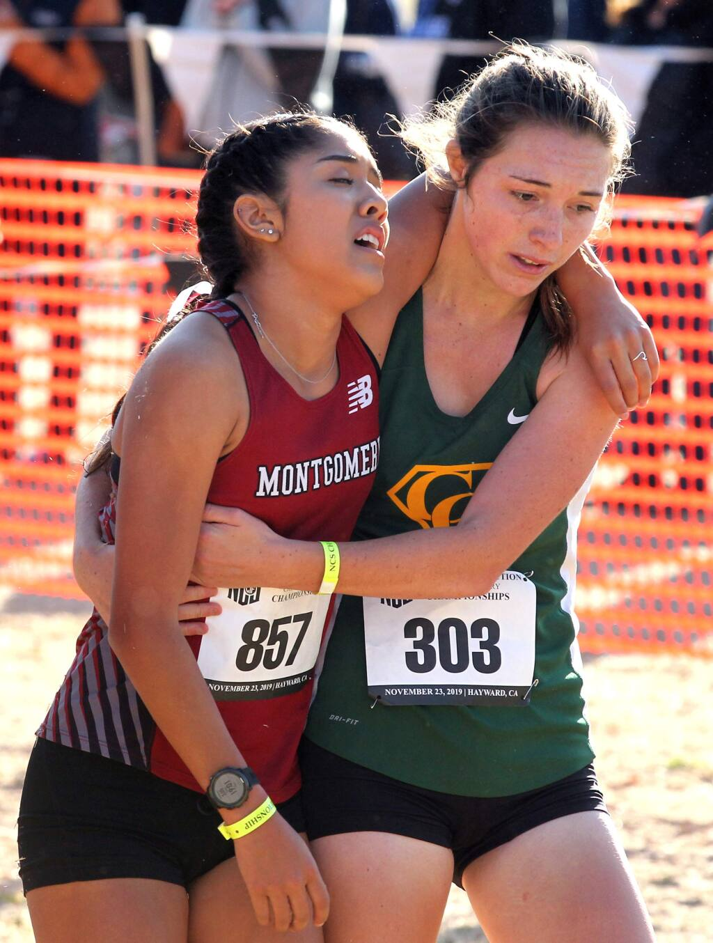 Mariah Briceno of Montgomery High, left, is hugged by Casa Grande's Emma Baswell after they finished the Division 3 girls race at the NCS cross country championships in Hayward on Saturday, Nov. 23, 2019. (Photo by Darryl Bush / For The Press Democrat)