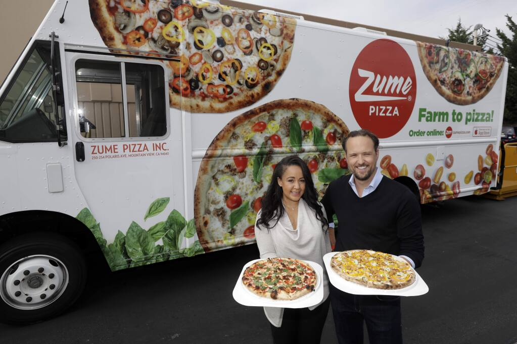 FILE - In this Aug. 29, 2016, file photo, CEO and co-founder Julia Collins, left, and co-founder Alex Garden pose for a photo in front of one of the company's delivery trucks at Zume Pizza in Mountain View, Calif. It has not been a good week for robots in the San Francisco Bay Area. A Silicon Valley company that used robots to make its pizzas closed this week and three coffee shops in downtown San Francisco that used robots as baristas also shuttered. Zume Pizza said it is cutting 172 jobs in Mountain View, and eliminating another 80 jobs at its facility in San Francisco. Zume Chief Executive Alex Garden made the announcement about Zume in an email to company employees on Wednesday, Jan. 8, 2020, the Mercury News reported. (AP Photo/Marcio Jose Sanchez, File)
