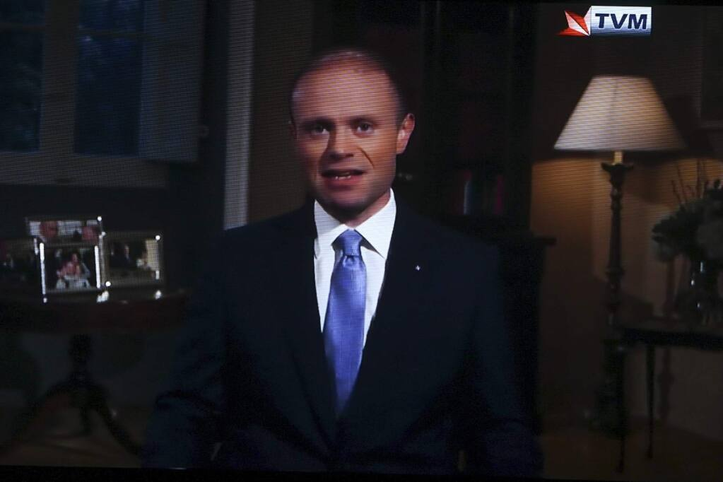 This photo shows a TV set displaying the broadcast of Maltese Prime Minister Joseph Muscat addressing the nation, Sunday, Dec. 1, 2019. Maltese Prime Minister Joseph Muscat told the nation Sunday night that he would resign in January following pressure from angry citizens for the truth about the 2017 car bombing that killed a journalist. In a televised message, Muscat said he has informed Malta's president that he will quit as leader of the governing Labor Party on Jan. 12 and that 'in the days after I will resign as prime minister.' (AP Photo)
