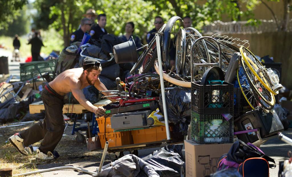 A homeless man tries to push a cobbled-together cart filled with his possession as Santa Rosa police officers closed a large encampment along the Joe Rodota Trail west of Dutton Ave. in Santa Rosa. (photo by John Burgess/The Press Democrat)