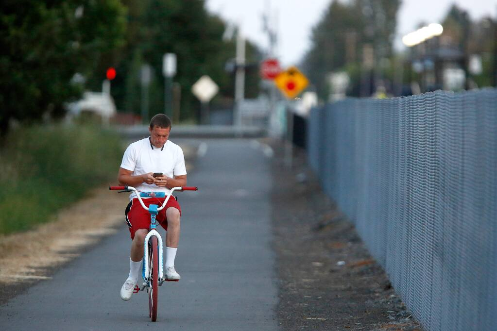 Brandon Simpson of Santa Rosa checks his cell phone while riding his bike along the path running parallel to the SMART train tracks in Rohnert Park, California, on Friday, June 8, 2018. (ALVIN JORNADA/ PD)
