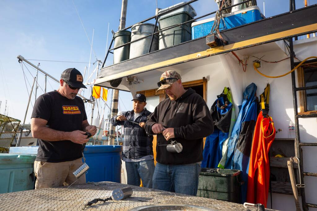 Deckhands Chris Ponts, left, Wilton Cruz, and Eric McGuire prepare bait canisters aboard the fishing vessel Blackhawk while the boat is docked at Spud Point Marina in Bodega Bay, California, on Thursday, January 30, 2020. (Alvin Jornada / The Press Democrat)