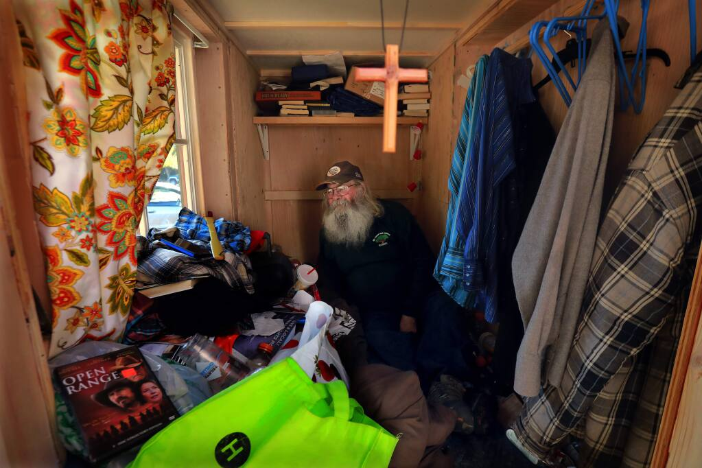 Former homeless man Russ Samson is now living in a closet-sided hut next to an office complex owned by former mayor Dave Berto. Samson has a bed window and storage under the bed for his books and clothing. (photo by John Burgess/The Press Democrat)