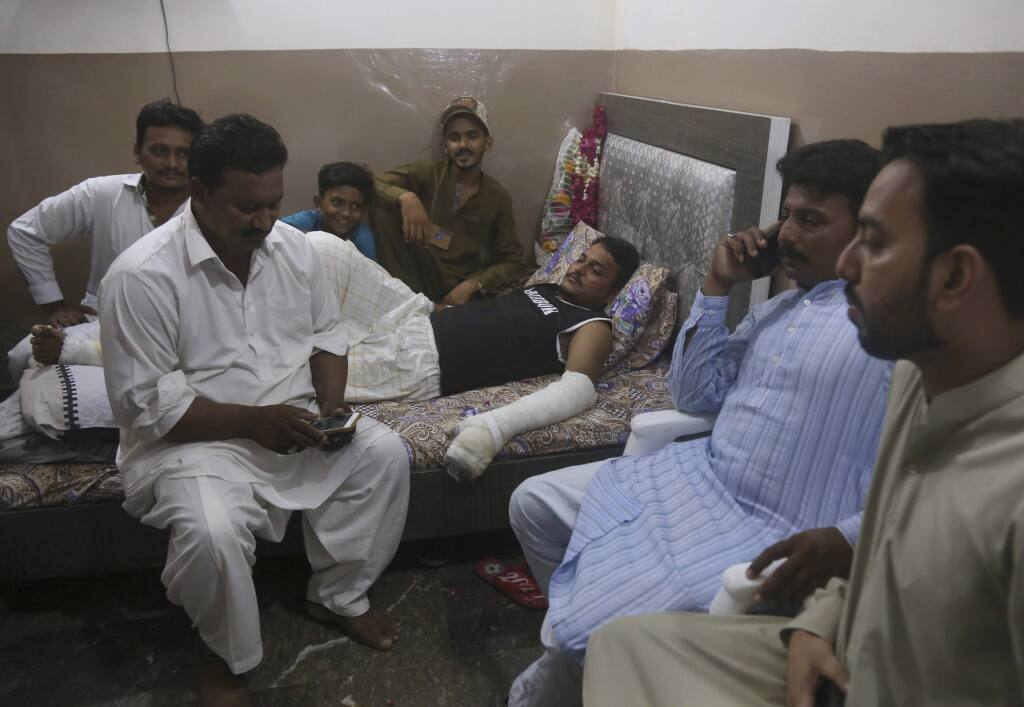 Relatives visit with Mohammad Zubair, a passenger who survived a plane crash, at his home in Karachi, Pakistan, Saturday, May 23, 2020. When the plane jolted violently, Zubair thought it was turbulence. Then the pilot came on the intercom to warn that the landing could be 'troublesome.' Moments later, the Pakistan International Airlines flight crashed into a crowded neighborhood near Karachi's international airport. (AP Photo/Fareed Khan)