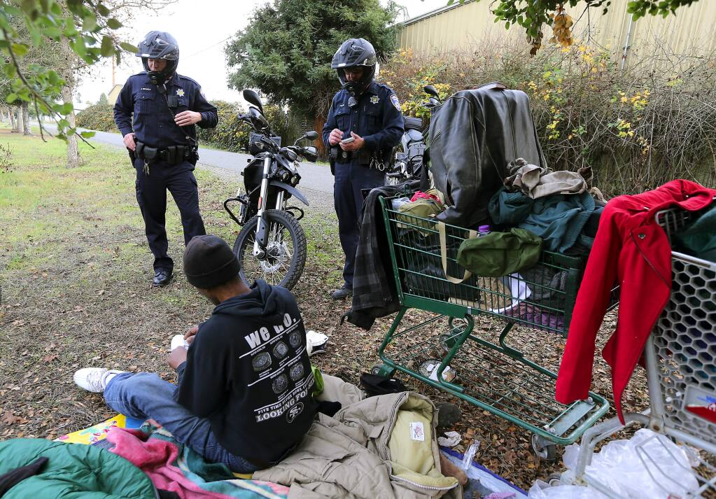 Santa Rosa police officers Jason Brandt, left, and Steve Pehlke use new electric motorcycles to quietly patrol the Joe Radota trail where they questioned a homeless man about his plans for finding shelter. (JOHN BURGESS / The Press Democrat)