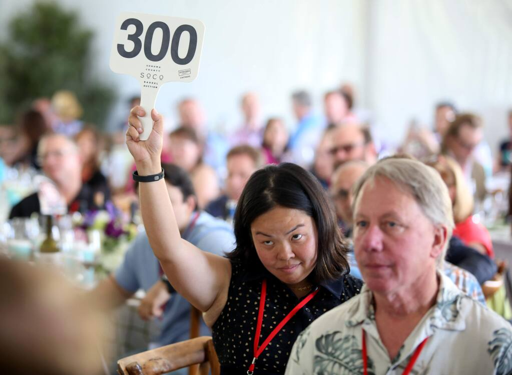 PHOTO: 1 BY CRISTA JEREMIASON/ THE PRESS DEMOCRAT -Limeng Stroh, bidding on behalf of Glen Knight, won a lot with a bid of $24,000 on Friday during the Sonoma County Barrel Auction in Santa Rosa.