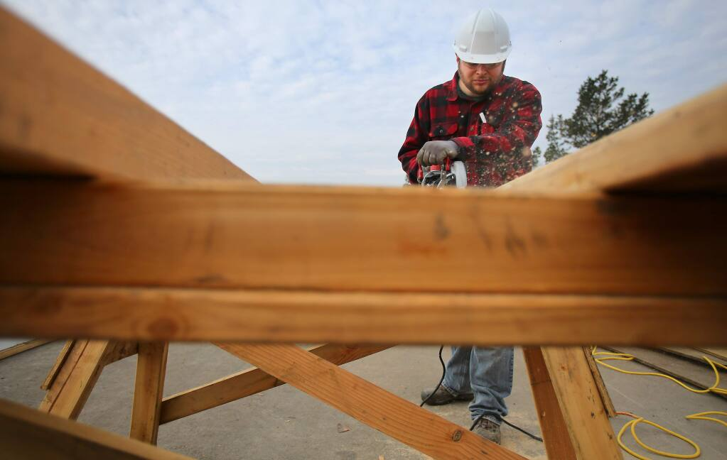 Ben Merilatt cuts wood at the construction site where his family will have a new home, in Santa Rosa on Thursday, January 15, 2015. The Merilatt's are one of 60 families working their way into the Catalina Townhomes, Burbank Housing's latest affordable housing project. By helping to build the housing project, families receive a $20,000 credit on the price of the home. (Christopher Chung/ The Press Democrat