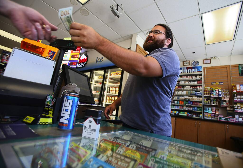 Aman Gill sells a pack of cigarettes to a customer at his family's Fast Lane gas station in Healdsburg, on Tuesday, June 30, 2015. The age limit to purchase cigarettes and tobacco products in Healdsburg has been raised to 21.(Christopher Chung/ The Press Democrat)