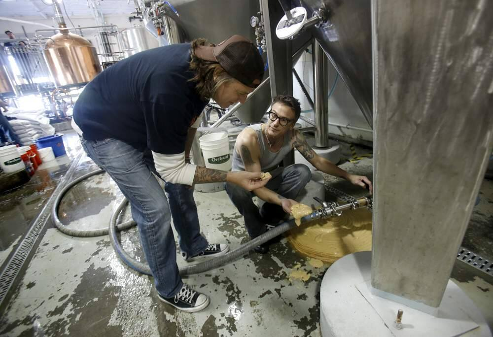Brothers and co-owners Jake, left, and Joel Johnson look at the yeast of a red rye beer as it drains from a fermenter at the newly opened 101 North Brewing Company on Thursday, April 25, 2013 in Petaluma, California. (BETH SCHLANKER/ The Press Democrat)