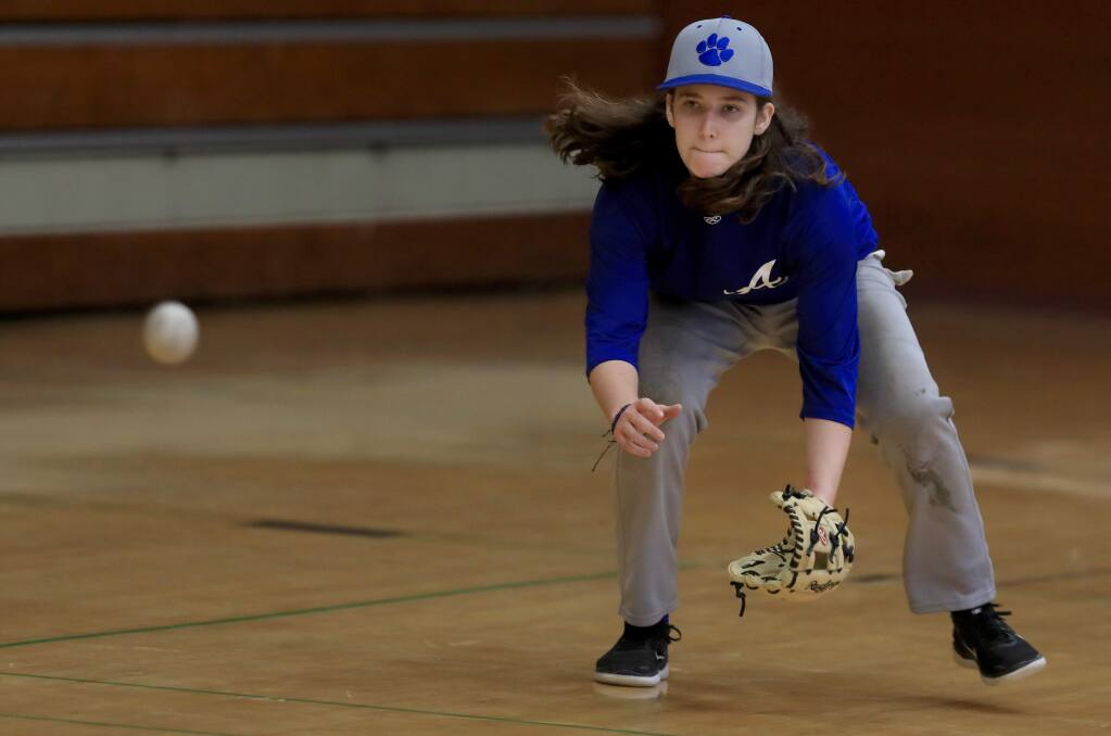Kaija Bazzano, a junior at Analy High School, fields grounders during a rainy day workout on Tuesday, March 5, 2019. Bazzano is a member of the varsity baseball team. (Kent Porter / The Press Democrat)