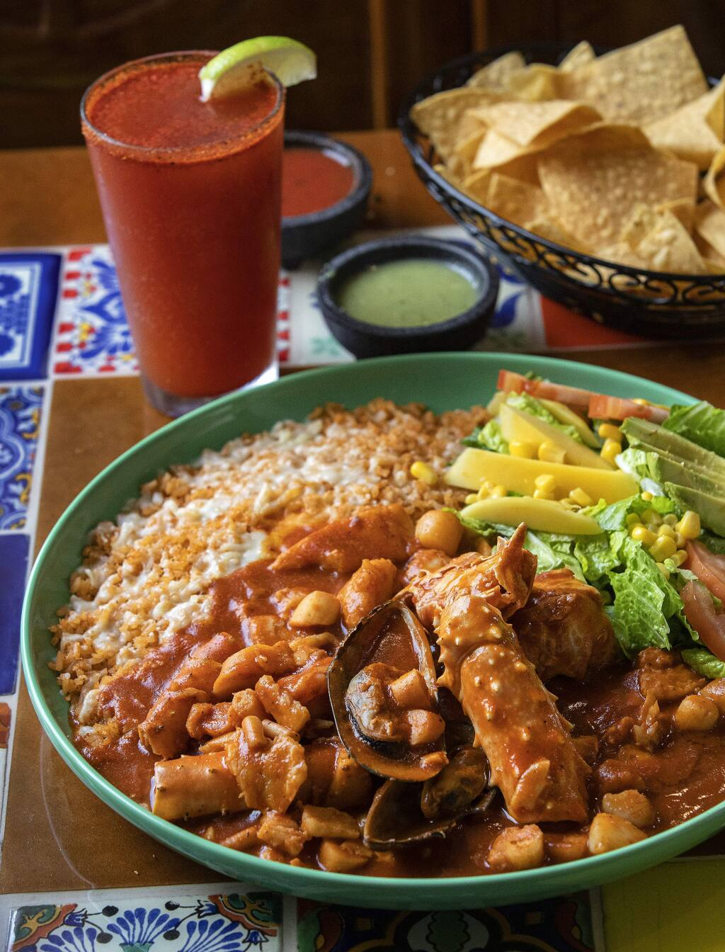 Mariscos Jarochos of prawns, octopus, scallops, crab legs, fish and green mussels in red sauce with a Michelada spiced beer from the La Hacienda Mexican Grill in Sonoma. (John Burgess/The Press Democrat)