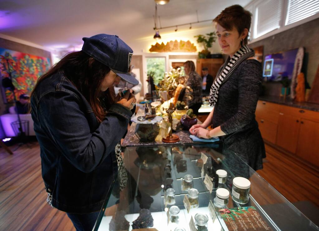 Raenell Daniels, left, of Lake County smells a jar of Jessy Girl marijuana buds as bud tender Anelisa Jordan looks on, at Emerald Pharms cannabis dispensary in Hopland, California, on Thursday, March 1, 2018. (Alvin Jornada / The Press Democrat)