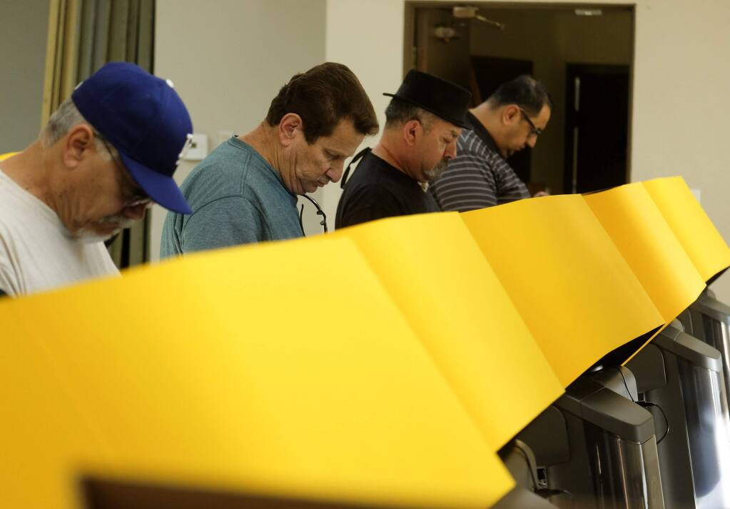 FILE - In this Tuesday, March 3, 2020 file photo, voters cast their ballots in the California Primary Super Tuesday at a voting center in Rosemead, Calif. California's top election official says Los Angeles County should mail ballots to its 5.5 million registered voters at least 29 days ahead of the November general election to avoid the lengthy delays that plagued polling places in the nation's most populous county on Super Tuesday. (AP Photo/Ringo H.W. Chiu, File)