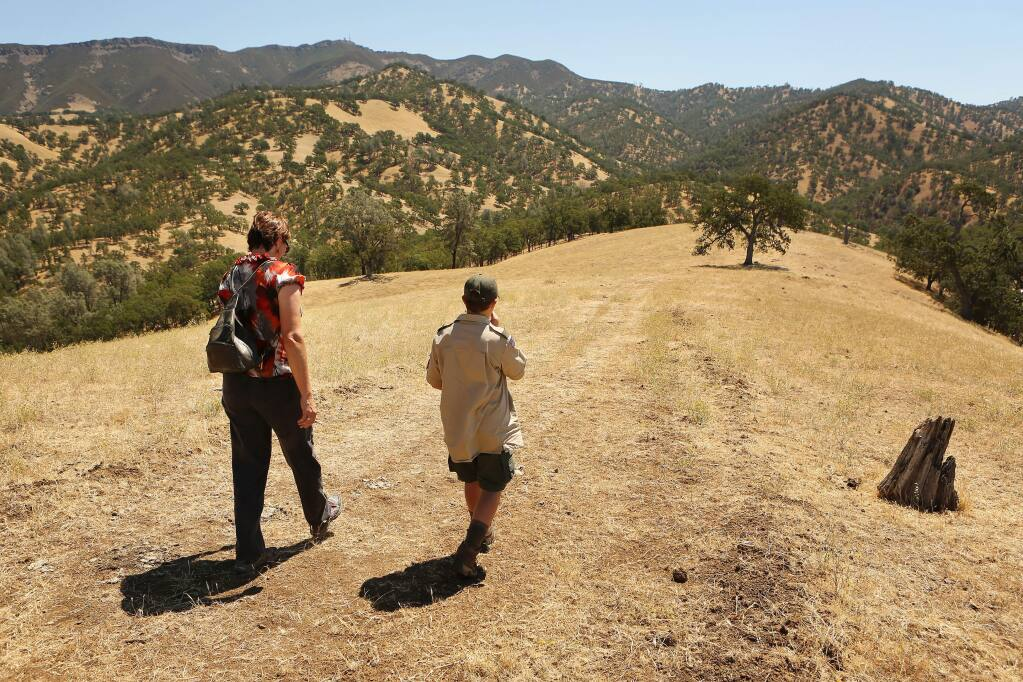 (File photo) Chistina Roberts and her son Darren hike to the top of the ridge line by her family's property at Running Deer Ranch by Lake Berryessa on Friday, July 26, 2013. Robert's mother Judy Ahmann testified to Congress to consider a bill to create a Berryessa Snow Mountain National Conservation Area. (Conner Jay/The Press Democrat)
