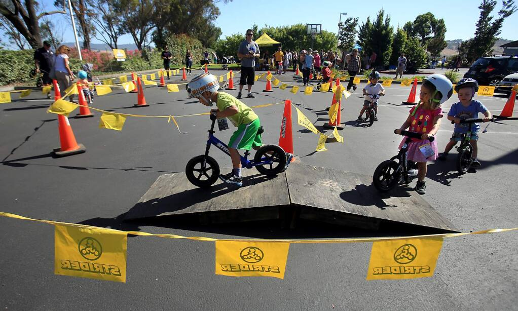Strider bikes and Bell helmet's were part of a giveaway at CamelBak headquarters in Petaluma, Wednesday June 29, 2016. About 80 bikes were given out to kids in an order to learn balance before graduating to pedal bikes. (Kent Porter / Press Democrat) 2016