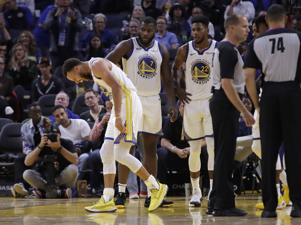 The Golden State Warriors' Stephen Curry, left, grimaces after the Phoenix Suns' Aron Baynes fell onto him during the second half Wednesday, Oct. 30, 2019, in San Francisco. Curry left the game. (AP Photo/Ben Margot)