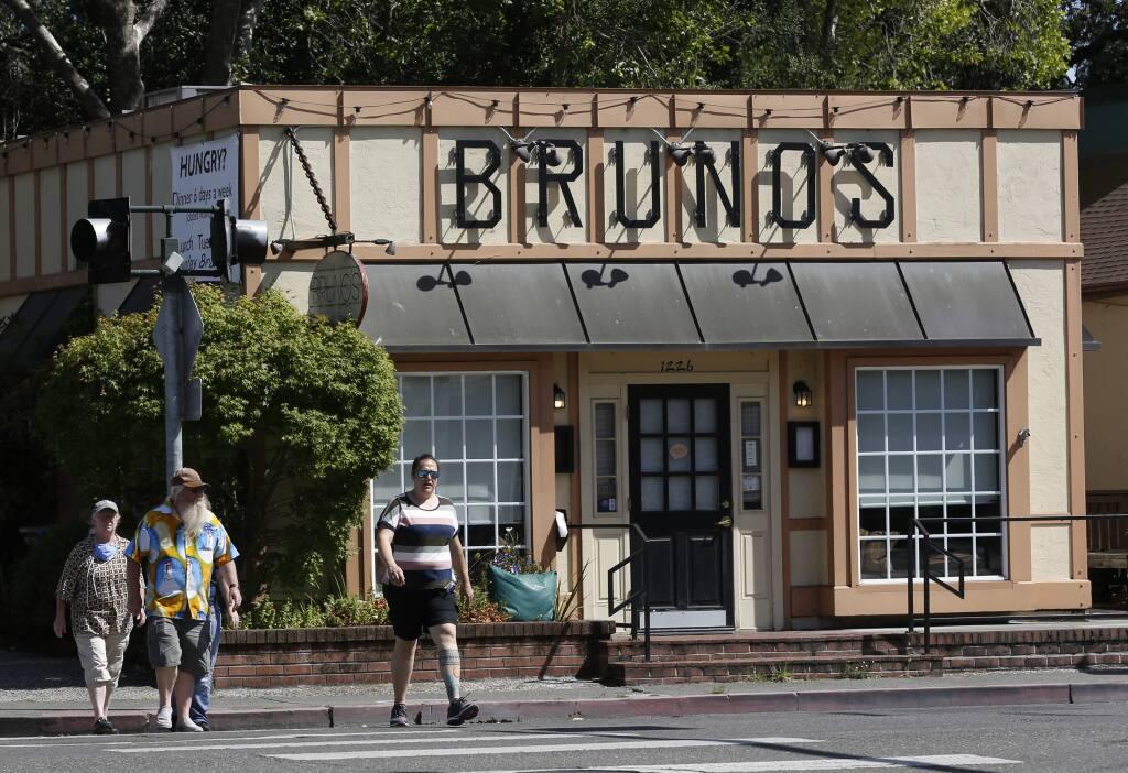 On June 14, 2020, pedestrians walks past Bruno's on Fourth restaurant, which is now permanently closed. (BETH SCHLANKER/ The Press Democrat)