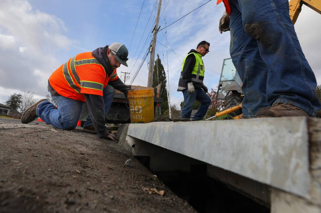 Town of Windsor employees Trevor Silva, left, and Lennie Morrell work on the repair and maintenance of a storm drain on the corner of Shiloh Road and Old Redwood Highway in Windsor on Tuesday, Jan. 14, 2020. (CHRISTOPHER CHUNG/PD)