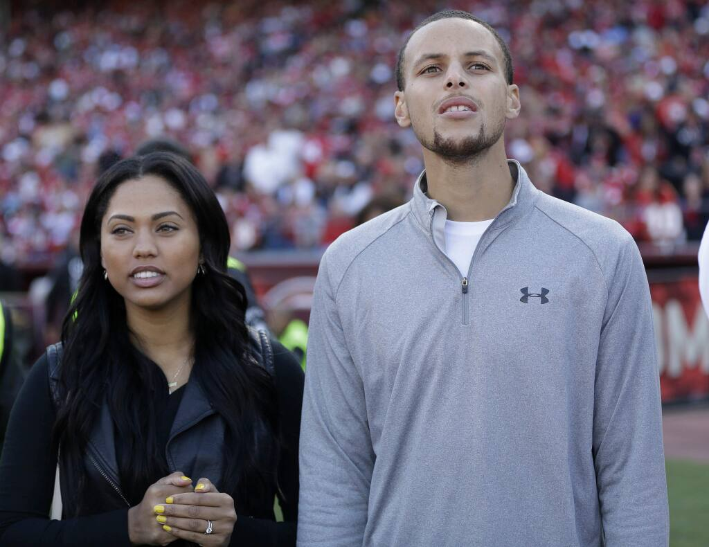 FILE - In this Nov. 10, 2013, file photo, Golden State Warriors player Stephen Curry, right, and his wife Ayesha Curry watch as the San Francisco 49ers play the Carolina Panthers during the third quarter of an NFL football game in San Francisco. Ayesha Curry told People magazine in an interview published online on July 6, 2016, that she regrets calling the NBA rigged in a tweet posted after the Warriors lost to the Cavaliers in Game 6 of the NBA finals, (AP Photo/Marcio Jose Sanchez, File)
