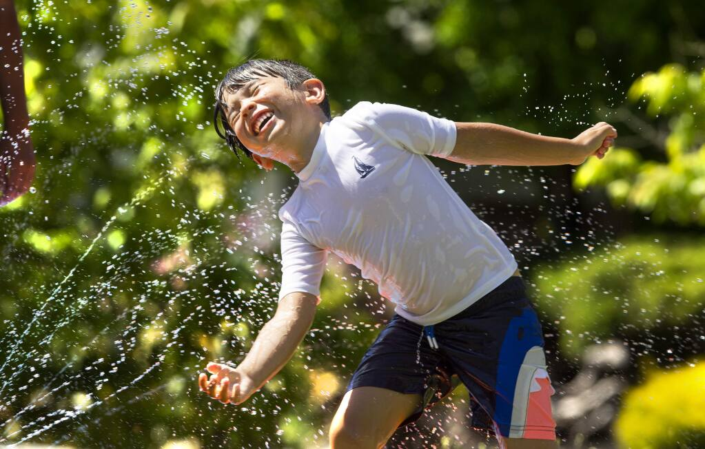 Cohen Parker delights int he spray of his Slip 'N Slide on the grass of his Santa Rosa home on Tuesday, March 26, 2020. (John Burgess/The Press Democrat)