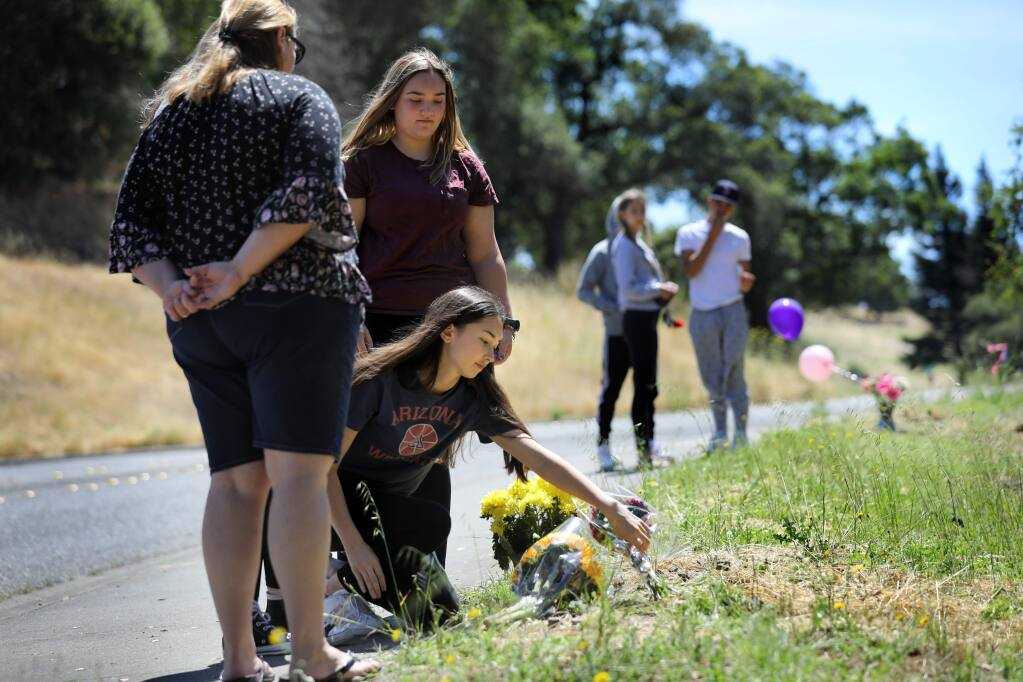 Rachel Fong, 16, joined by her friend Abigail Rasore, 15, rear, and Abigail's mother Jennifer Rasore, places a bouquet of flowers on the ground as they remember their 16-year-old friend who died in a car accident at the corner of Thomas Lake Harris Drive and Skyfarm Drive in Santa Rosa on Monday, July 1, 2019. Click through to see photos from the most-read stories of 2019. (BETH SCHLANKER/ PD)