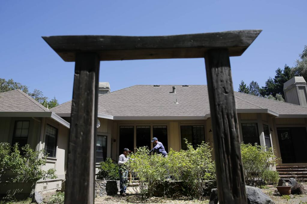 Alfredo Moreno, left, and Daniel Reyes from D R C Four Seasons Landscape Inc, prune the rose bushes at a home that was formerly rented and is now being sold in Santa Rosa on Thursday, June 14, 2018. (Beth Schlanker/ The Press Democrat)